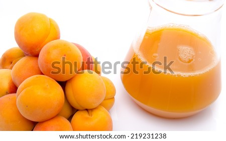 Heap of apricots and a jug of apricot juice, isolated on white