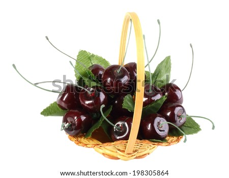 Heap of artificial several cherries with leafs in yellow basket. Isolated on white background. Close-up. Studio photography. - stock photo