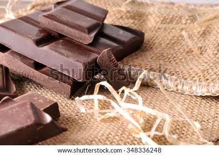 Heap of artisan portions chocolate on burlap sack and straw decoration. Horizontal composition. Front view. Close up. - stock photo