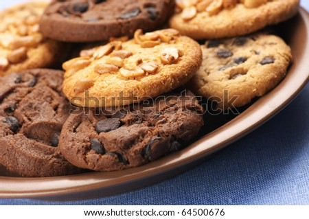 Heap of assorted cookies in brown ceramic plate on blue cloth. - stock photo