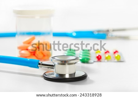Heap of assorted pill packages. Phonendoscope and pill - stock photo