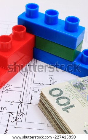 Heap of banknotes and wall of plastic colorful building blocks lying on construction drawing of house, concept of building house - stock photo