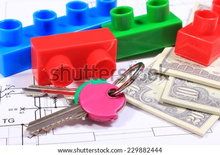 Heap of banknotes, home keys and plastic colorful building blocks lying on construction drawing of house, concept of building house - stock photo