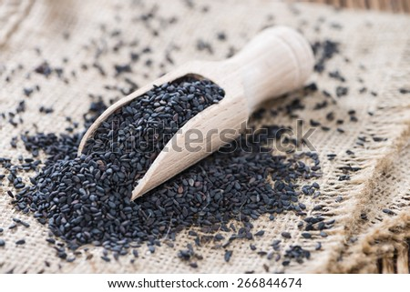 Heap of black Sesame (close-up shot) on wooden background - stock photo