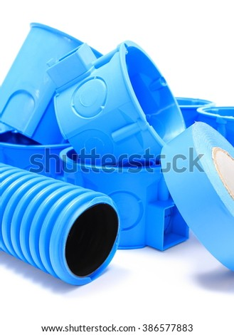 Heap of blue electrical boxes and components for use in electrical installations, accessories for engineering jobs