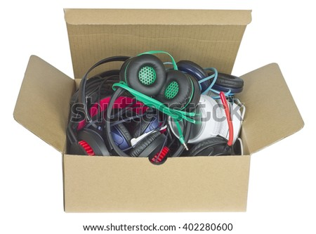Heap of broken musical devices earphones in paper box. Isolated with patch