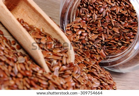 Heap of brown linseed, flax seeds spilling out of glass jar on wooden background, concept for healthy nutrition