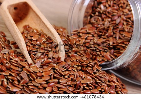 Heap of brown linseed, flax seeds spilling out of glass jar on wooden background, concept of healthy nutrition