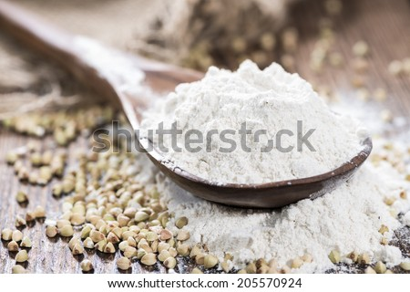 Heap of Buckwheat Flour (close-up shot) with some grains on wooden background - stock photo