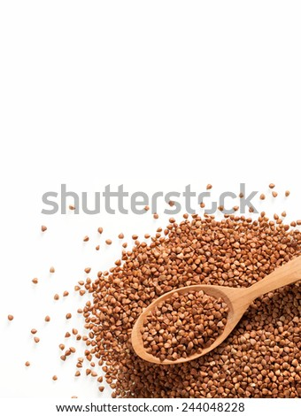 Heap of buckwheat groats and wooden spoon / premium buckwheat groats on white background  - stock photo