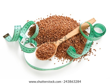 Heap of buckwheat groats / premium buckwheat groats on white background with wooden spoon and measuring tape  - stock photo