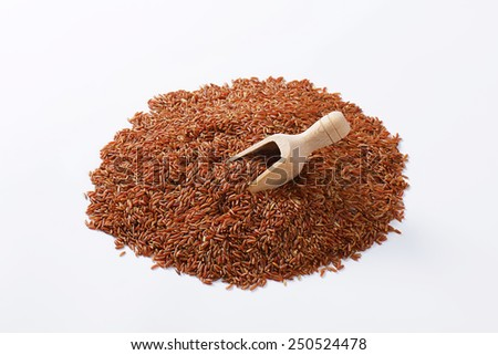 Heap of Camargue red rice and wooden scoop - stock photo
