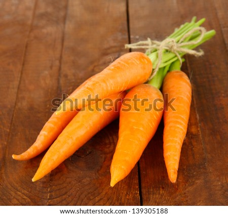 Heap of carrots on wooden background