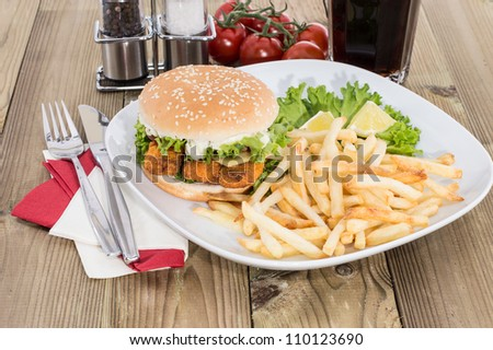 Heap of Chips with Fish Burger on wooden background - stock photo