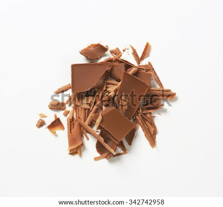 heap of chocolate shavings and slices on white background