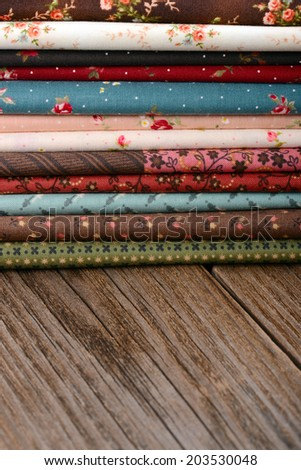 heap of cloth fabrics on wooden table - stock photo