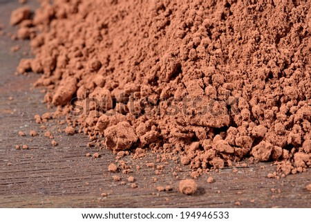 Heap of cocoa powder on a wooden background