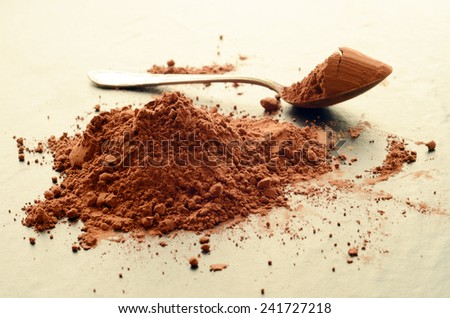 Heap of cocoa powder with a spoon on a table - stock photo