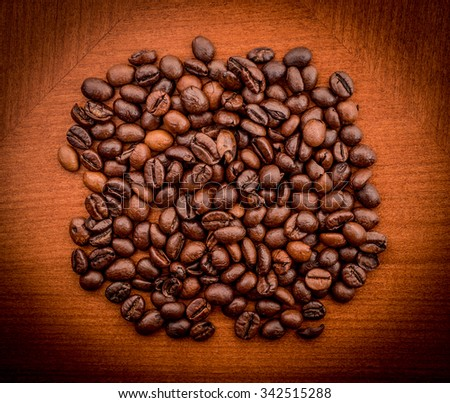 Heap of coffee beans on the brown table. Image taken from above.
