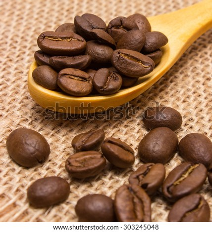 Heap of coffee beans on wooden spoon lying on jute canvas, coffee grains - stock photo