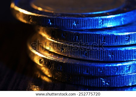 Heap of coins on wooden table, macro view - stock photo