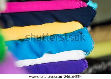 heap of colorful cloth fabrics, close up - stock photo