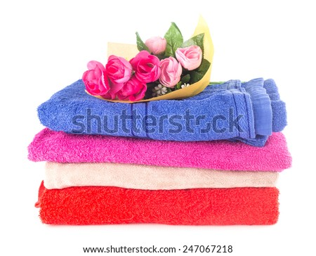 Heap of colorful dry cotton towels on white background