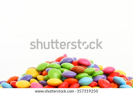heap of colorful smarties bordering lower part of picture on white background - stock photo