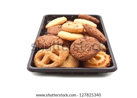 Heap of Cookie on black plastic tray, isolated on white - stock photo