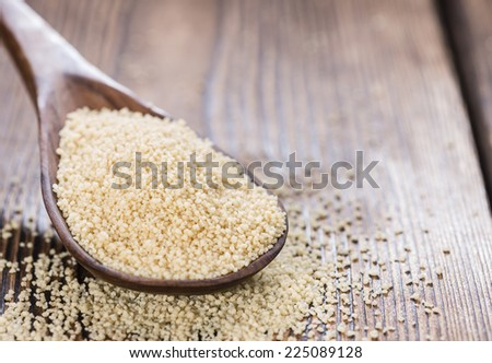 Heap of Couscous (close-up shot) on dark wooden background