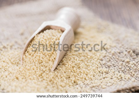 Heap of Couscous (close-up shot) on dark wooden background - stock photo