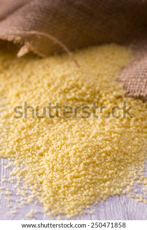 heap of couscous with linen bag on white wooden background - stock photo