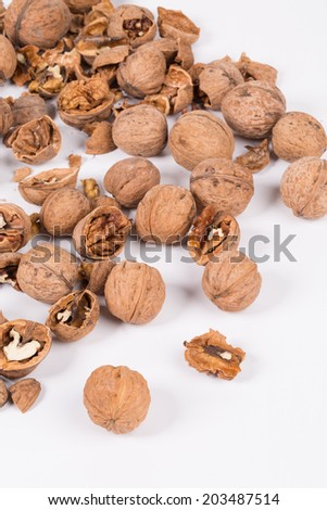 Heap of cracked walnuts. Isolated on a white background.