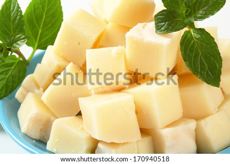 Heap of diced semi-firm cheese on plate