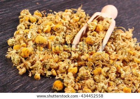 Heap of dried chamomile with wooden spoon lying on wooden surface, concept of healthy nutrition, herbalism and alternative medicine