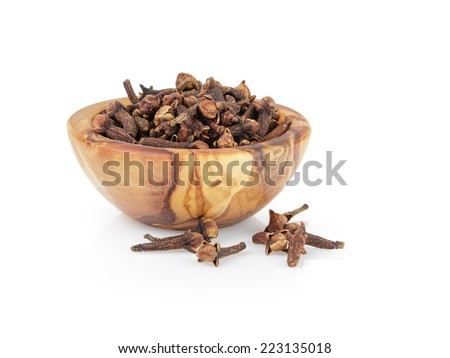 heap of dried cloves in bowl, isolated on white background - stock photo