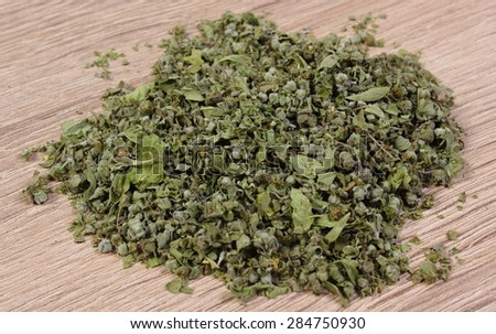 Heap of dried marjoram on wooden background, seasoning for cooking, concept for healthy nutrition - stock photo