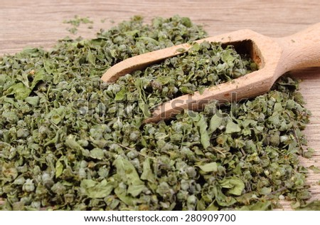 Heap of dried marjoram with wooden spoon on wooden background, seasoning for cooking, concept for healthy nutrition - stock photo
