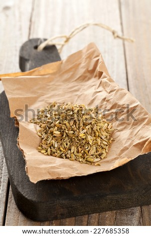 Heap of dried organic fennel seeds on wooden board on kitchen table - stock photo