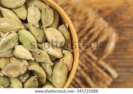 heap of dry cardamom on burlap napkin - stock photo