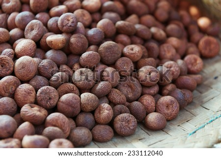 Heap of dry full nutmegs on open market - stock photo