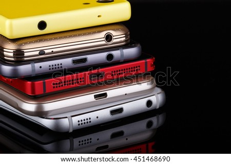 Heap of electronical devices close up - smartphones on black background - stock photo