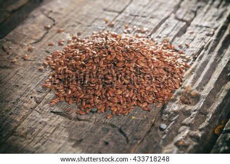 Heap of flax seeds, on wooden surface. - stock photo