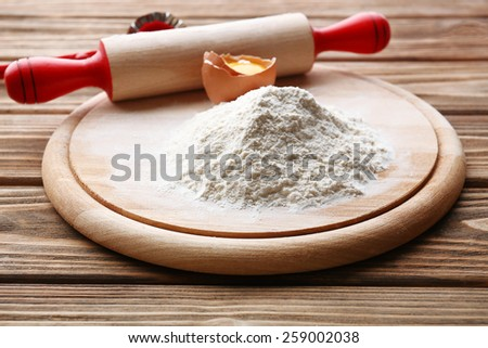 Heap of flour on cutting board with egg and plunger on wooden table - stock photo