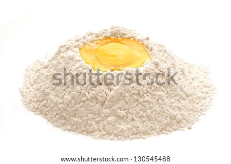 heap of flour with raw egg over white background - stock photo