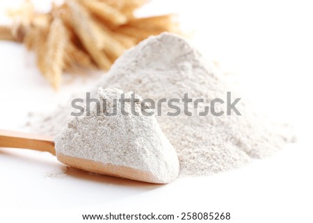 Heap of flour with wooden spoon and ears close up - stock photo
