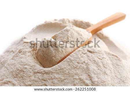 Heap of flour with wooden spoon isolated on white - stock photo