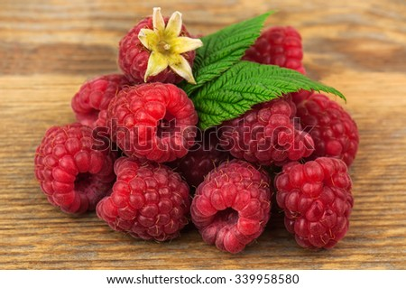heap of fresh and sweet raspberries with leaves  - stock photo