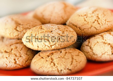 heap of fresh appetizing oatmeal cookies on red plate - stock photo
