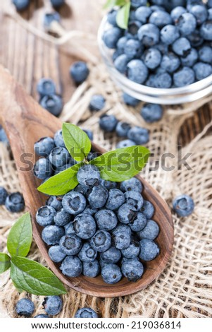 Heap of fresh Blueberries on a Wooden Spoon (close-up shot)